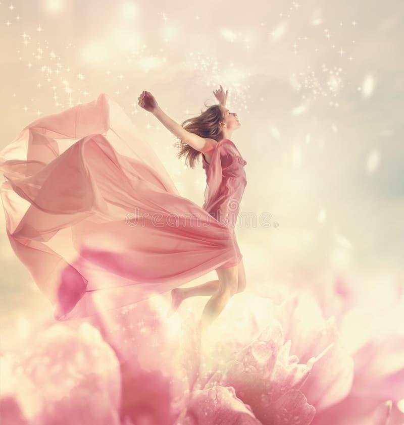 Jovem mulher bonita que salta na flor gigante fotos de stock royalty free