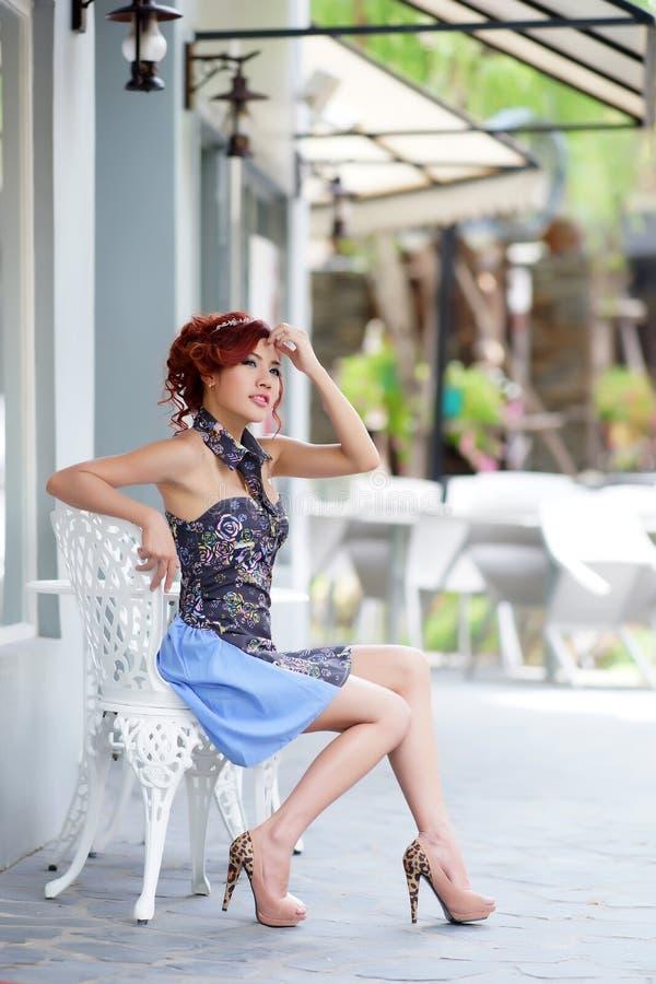 Jovem mulher bonita que senta-se apenas no café da rua imagens de stock