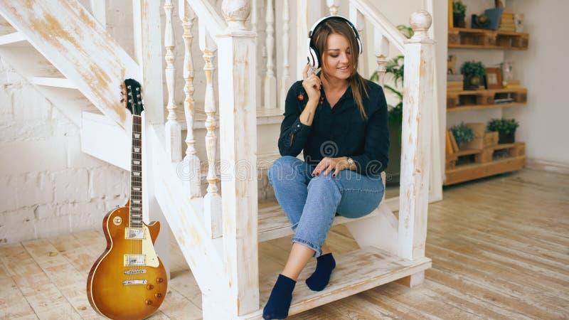 A jovem mulher bonita que senta-se em escadas escuta música nos fones de ouvido em casa dentro foto de stock royalty free