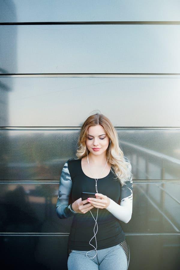 Jovem mulher bonita que senta-se em escadas no gym e que escuta imagem de stock