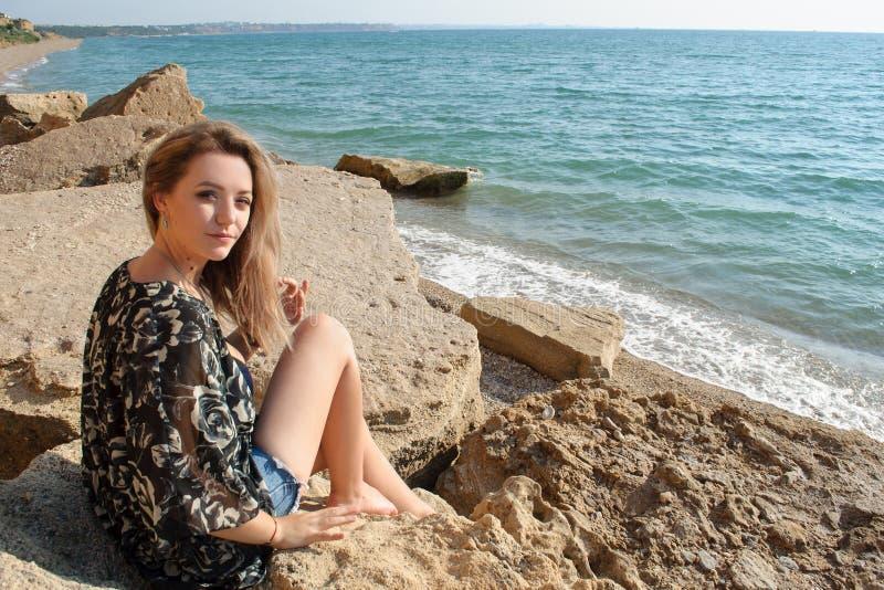Jovem mulher bonita que senta-se em rochas na costa fotografia de stock