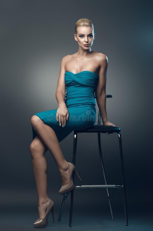 Jovem mulher bonita que senta-se em uma cadeira no estúdio dentro fotografia de stock