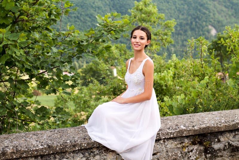 Jovem mulher bonita que senta-se em uma parede de pedra no vestido branco imagens de stock royalty free