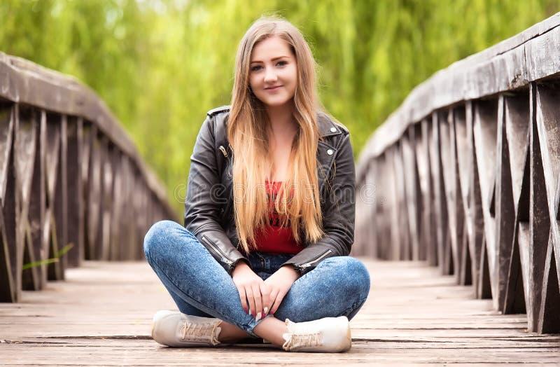 Jovem mulher bonita que senta-se em uma ponte de madeira fotografia de stock