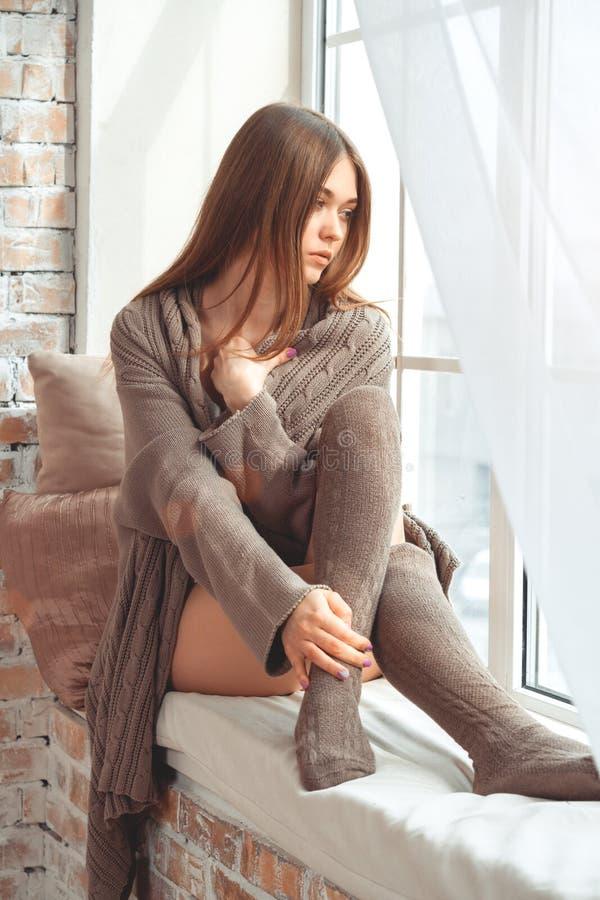 Jovem mulher bonita que senta-se em uma soleira imagem de stock