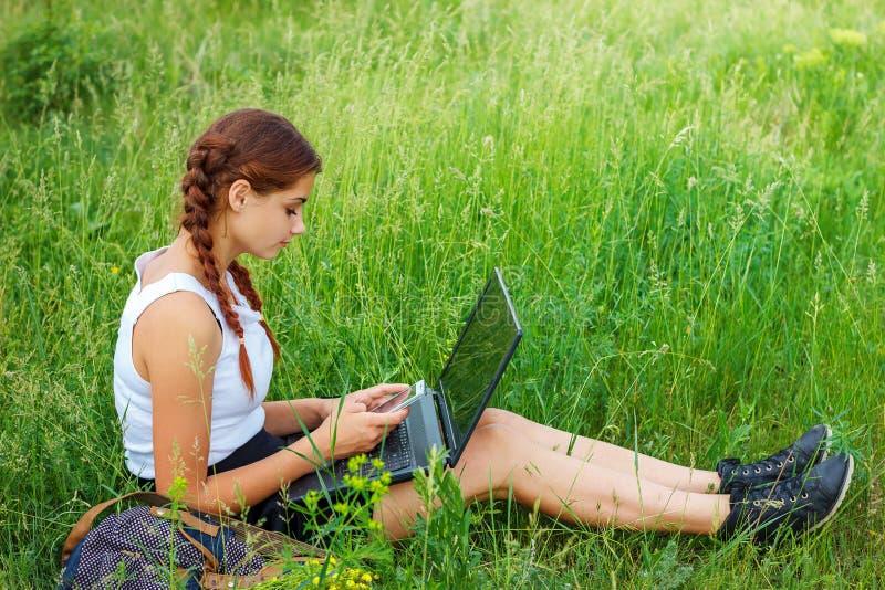 Jovem mulher bonita que senta-se na grama com portátil foto de stock