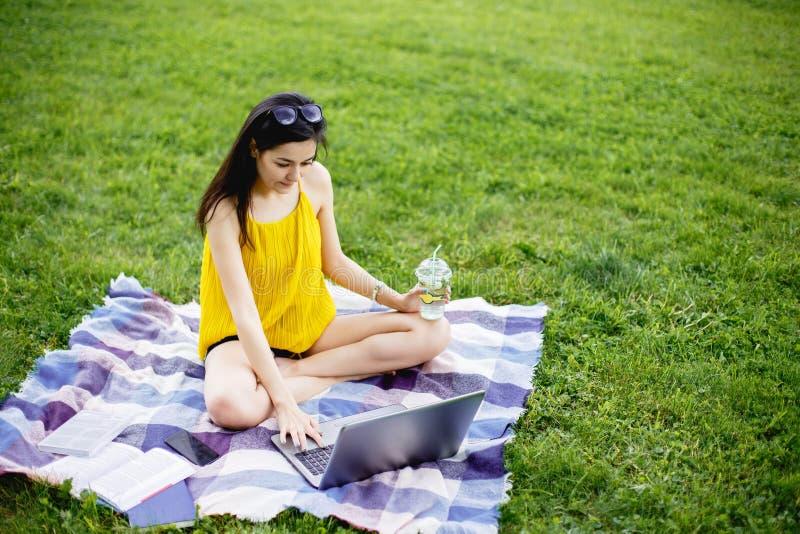 Jovem mulher bonita que senta-se na grama verde no parque com seu portátil Menina do estudante que olha o computador imagem de stock