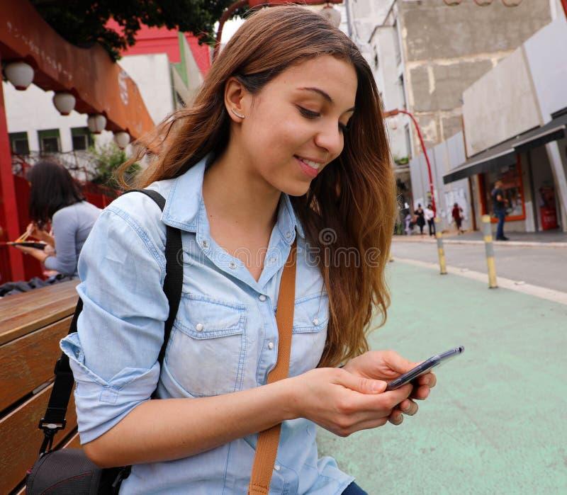 Jovem mulher bonita que senta-se na mensagem do banco da rua com telefone celular no Sao Paulo City, Brasil imagem de stock