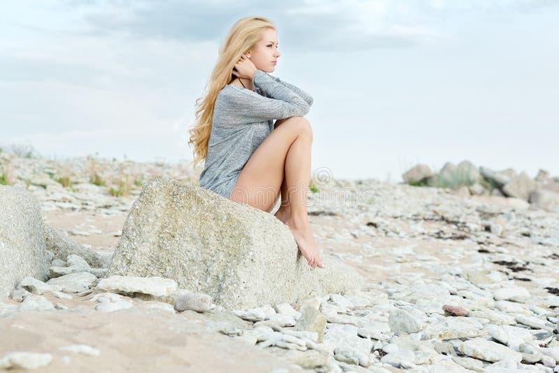 Jovem mulher bonita que senta-se na rocha imagem de stock