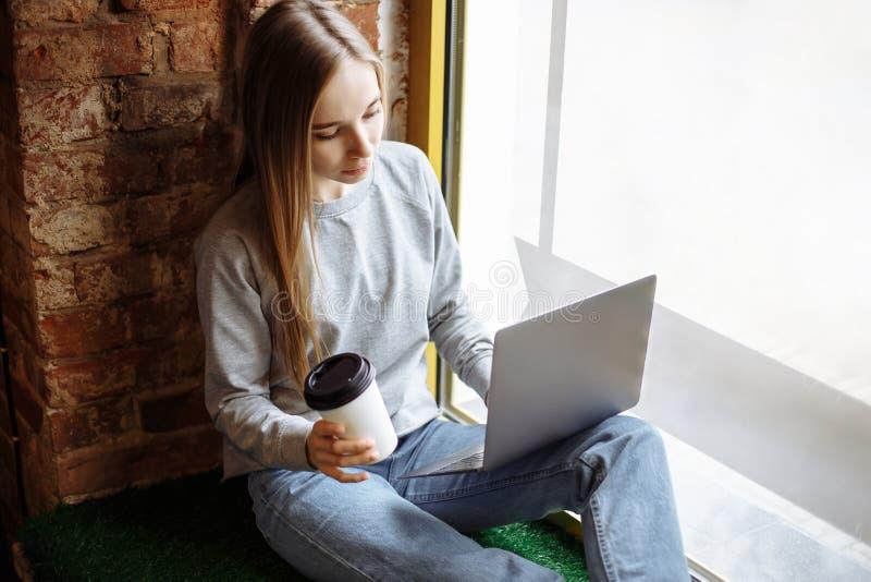 Jovem mulher bonita que senta-se na soleira e que usa o portátil imagens de stock royalty free