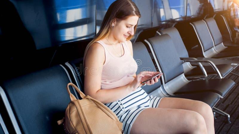 Jovem mulher bonita que senta-se no aeroporto ao esperar o Internet do voo e da consultação no telefone celular fotos de stock