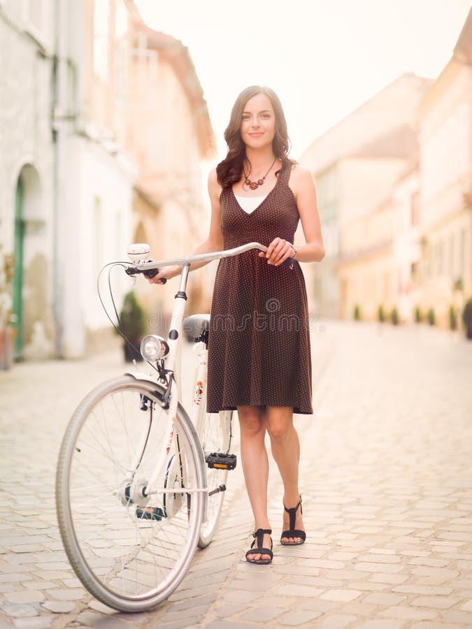 Jovem mulher bonita que sorri ao lado da bicicleta através da cidade foto de stock