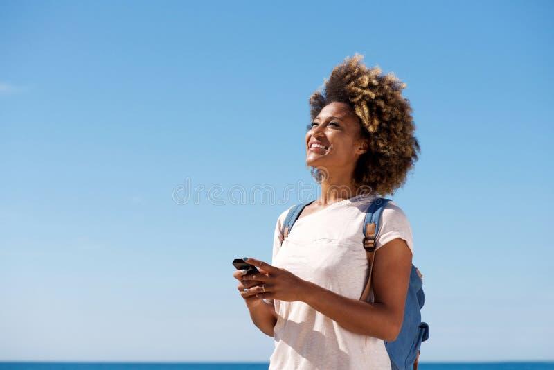 Jovem mulher bonita que sorri contra o céu fotografia de stock