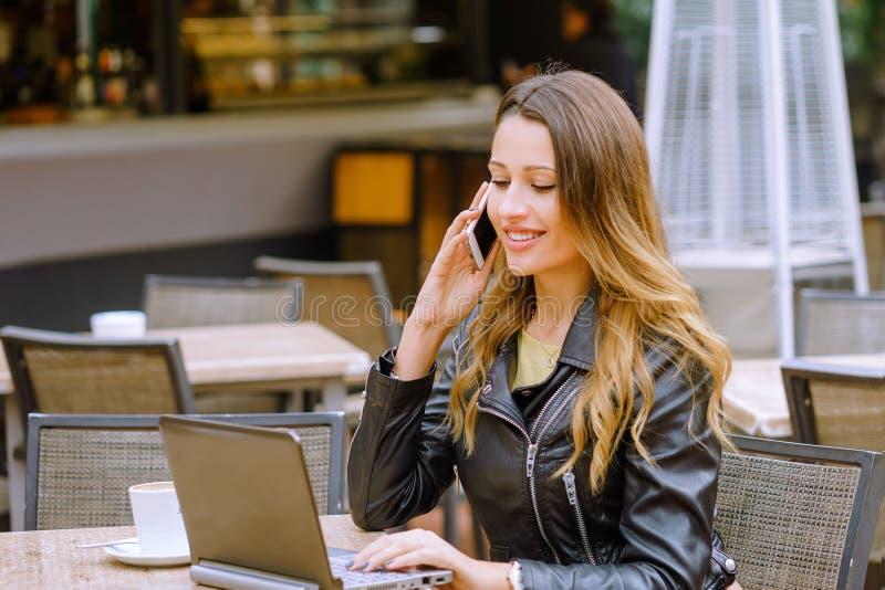 Jovem mulher bonita que sorri e que fala no smartphone fotografia de stock