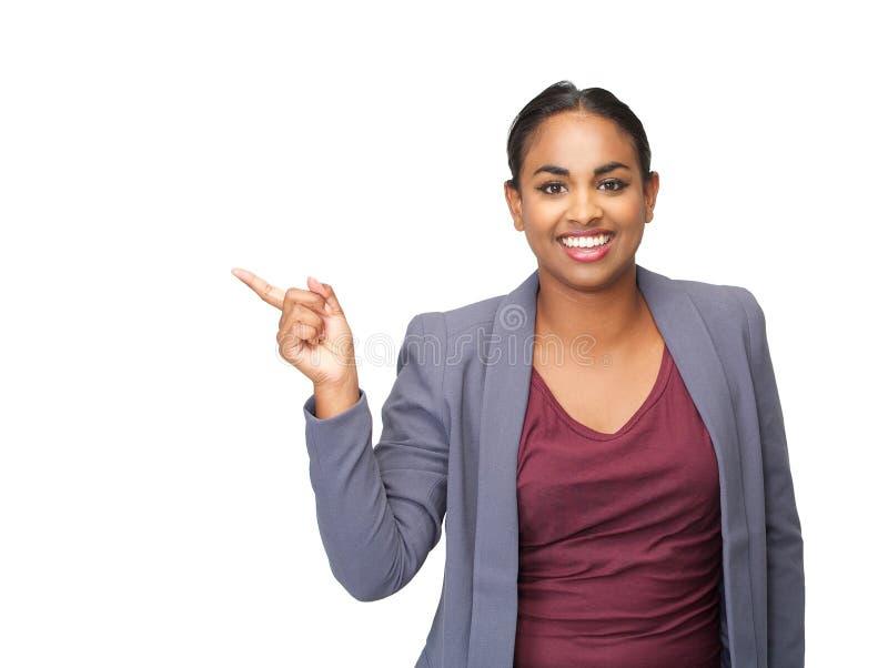 Jovem mulher bonita que sorri e que aponta o dedo foto de stock