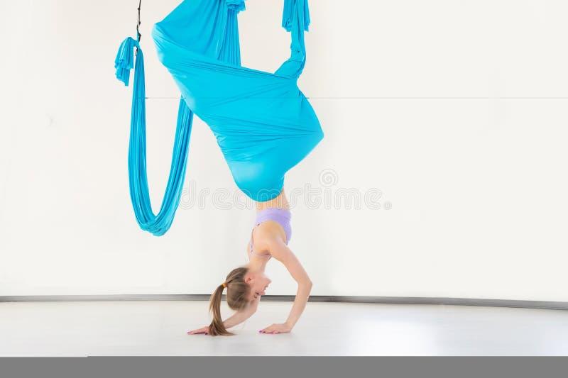 Jovem mulher bonita que sorri em praticar a ioga aero da mosca no estúdio branco em redes azuis Esticão do conceito fotos de stock royalty free