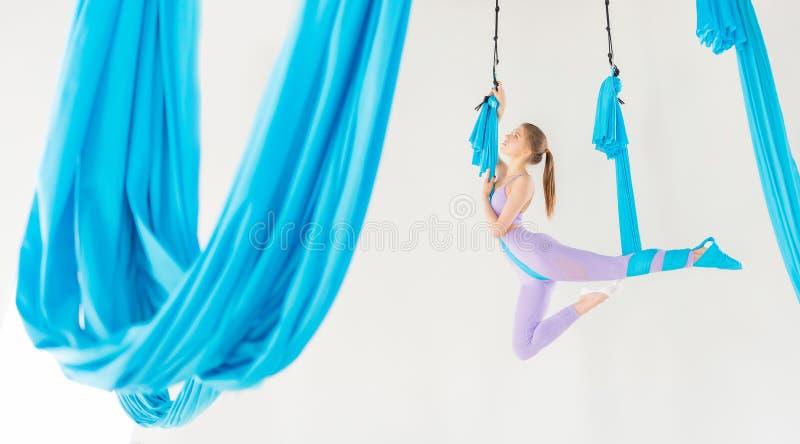 Jovem mulher bonita que sorri em praticar a ioga aero da mosca no estúdio branco em redes azuis Esticão do conceito imagens de stock royalty free