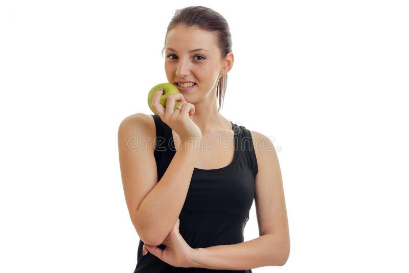 Jovem mulher bonita que sorri na câmera com a maçã verde em suas mãos imagem de stock