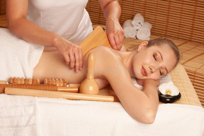Jovem mulher bonita que tem um tratamento maderotherapy da massagem no salão de beleza dos termas - bem-estar imagens de stock