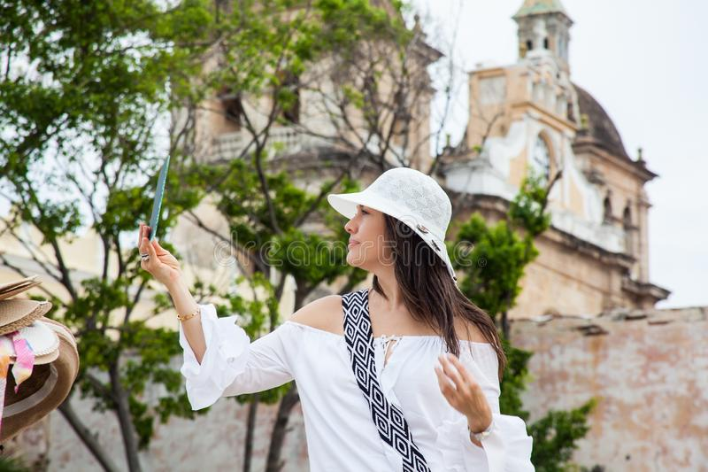 A jovem mulher bonita que tenta em chapéus comprar um de um vendedor ambulante em Cartagena de Índia murou a cidade fotografia de stock royalty free