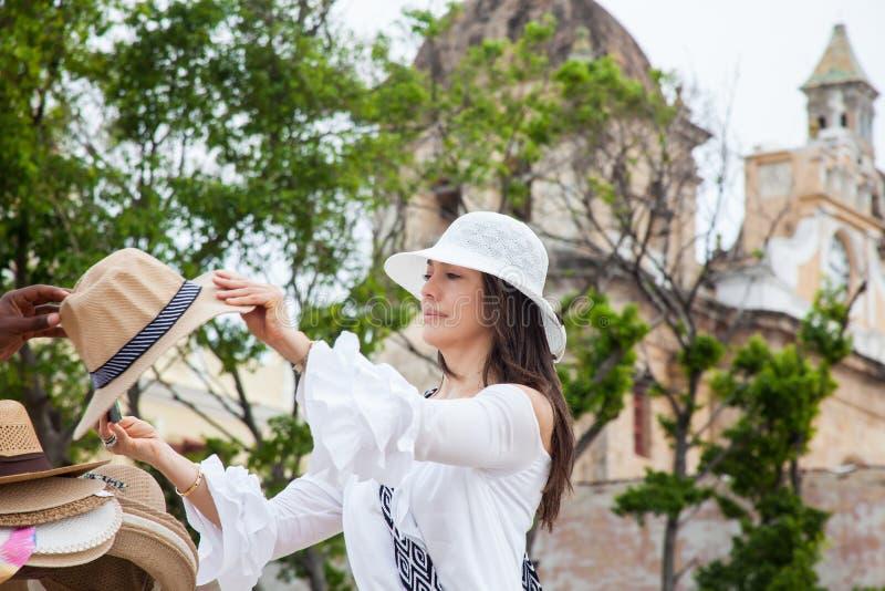 A jovem mulher bonita que tenta em chapéus comprar um de um vendedor ambulante em Cartagena de Índia murou a cidade imagem de stock