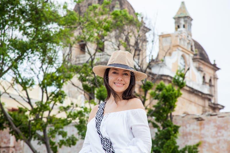 A jovem mulher bonita que tenta em chapéus comprar um de um vendedor ambulante em Cartagena de Índia murou a cidade fotos de stock royalty free