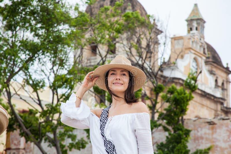 A jovem mulher bonita que tenta em chapéus comprar um de um vendedor ambulante em Cartagena de Índia murou a cidade foto de stock royalty free