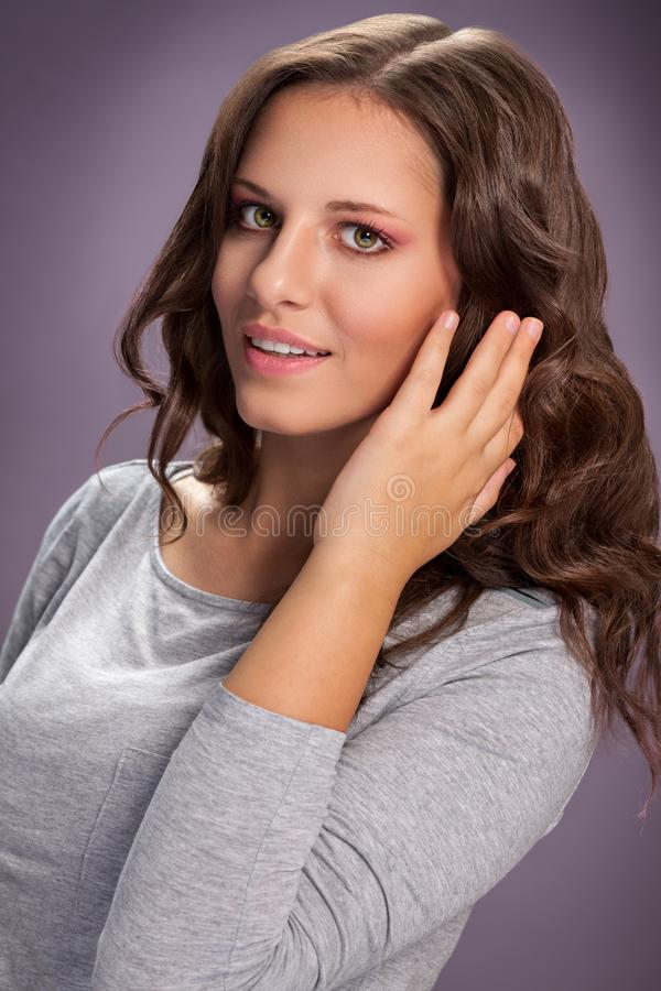 Jovem mulher bonita que toca em seu cabelo ondulado imagem de stock royalty free