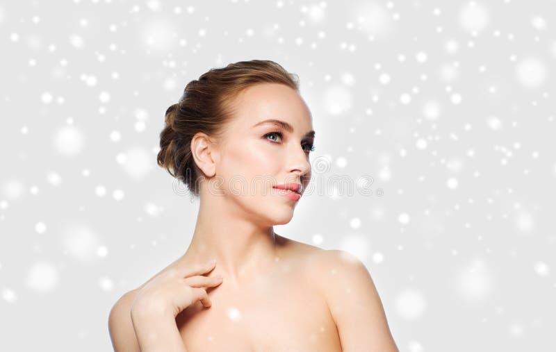 Jovem mulher bonita que toca em seu pescoço sobre a neve imagem de stock royalty free