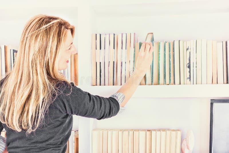 Jovem mulher bonita que toma um livro da prateleira na biblioteca imagens de stock