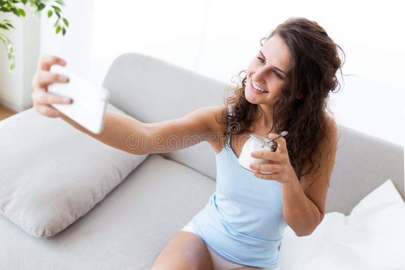 Jovem mulher bonita que toma um selfie ao comer o iogurte em casa fotos de stock
