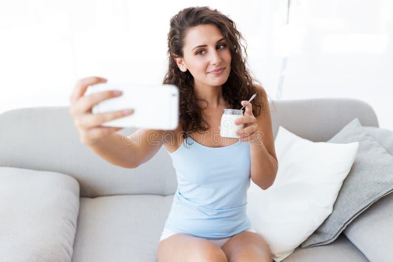 Jovem mulher bonita que toma um selfie ao comer o iogurte em casa imagem de stock