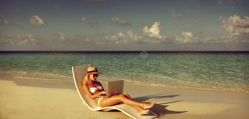 Jovem mulher bonita que trabalha com o portátil na praia tropical fotografia de stock