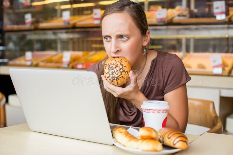 A jovem mulher bonita que trabalha no computador e come o pão Unheal foto de stock