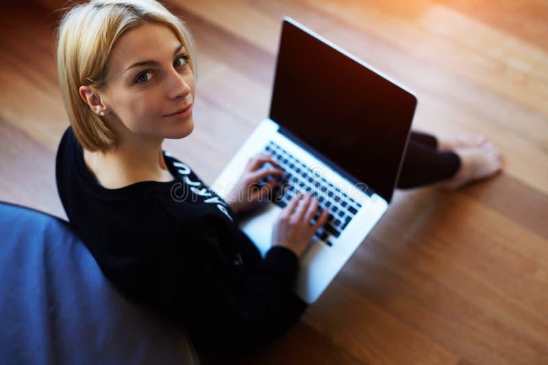 Jovem mulher bonita que trabalha no laptop em casa
