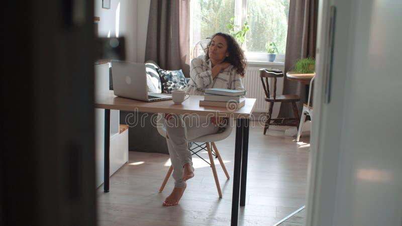 Jovem mulher bonita que trabalha no portátil moderno cercado por livros em casa foto de stock royalty free