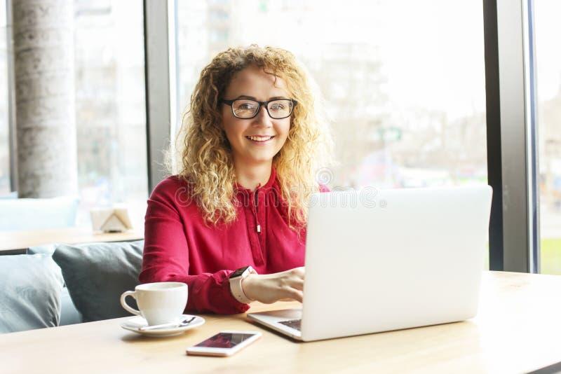 Jovem mulher bonita que trabalha remotamente em seu portátil elegante na cafetaria do moderno Freelancer fêmea feliz com pulso na fotografia de stock