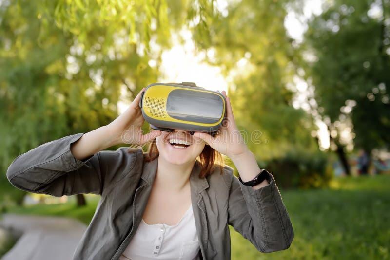 Jovem mulher bonita que usa os auriculares da realidade virtual exteriores VR, vidros de VR, experiência aumentada da realidade foto de stock