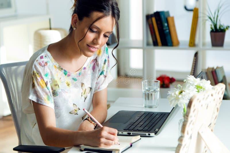 Jovem mulher bonita que usa seu portátil no escritório fotografia de stock royalty free