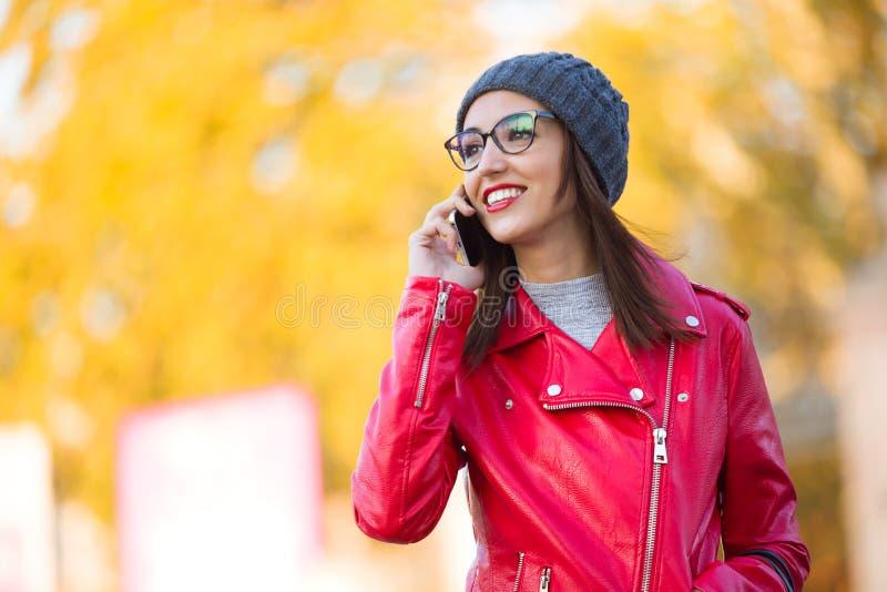 Jovem mulher bonita que usa seu telefone celular na cidade fotos de stock