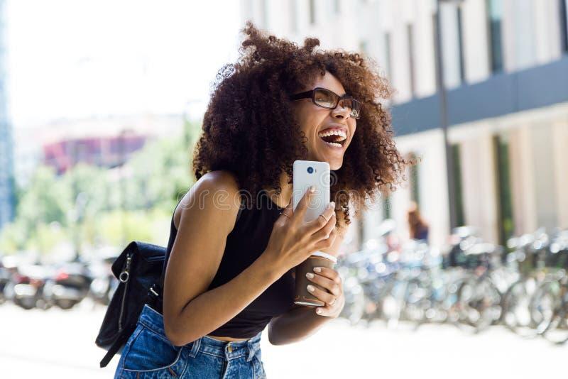 Jovem mulher bonita que usa seu telefone celular na rua imagens de stock