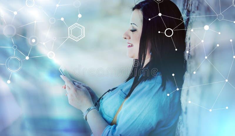 Jovem mulher bonita que usa seu telefone celular na rua, efeito da luz; exposição múltipla foto de stock royalty free