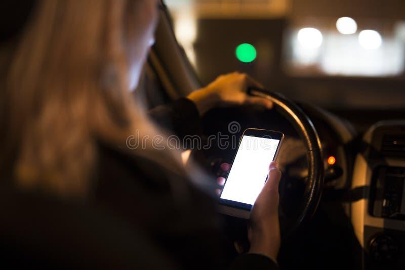 Jovem mulher bonita que usa seu telefone esperto ao conduzir seu carro na noite foto de stock