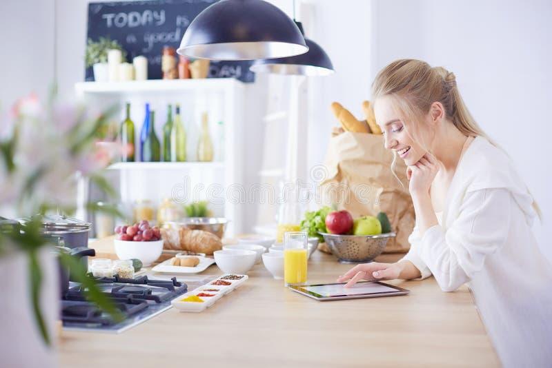 Jovem mulher bonita que usa uma tabuleta digital na cozinha imagem de stock
