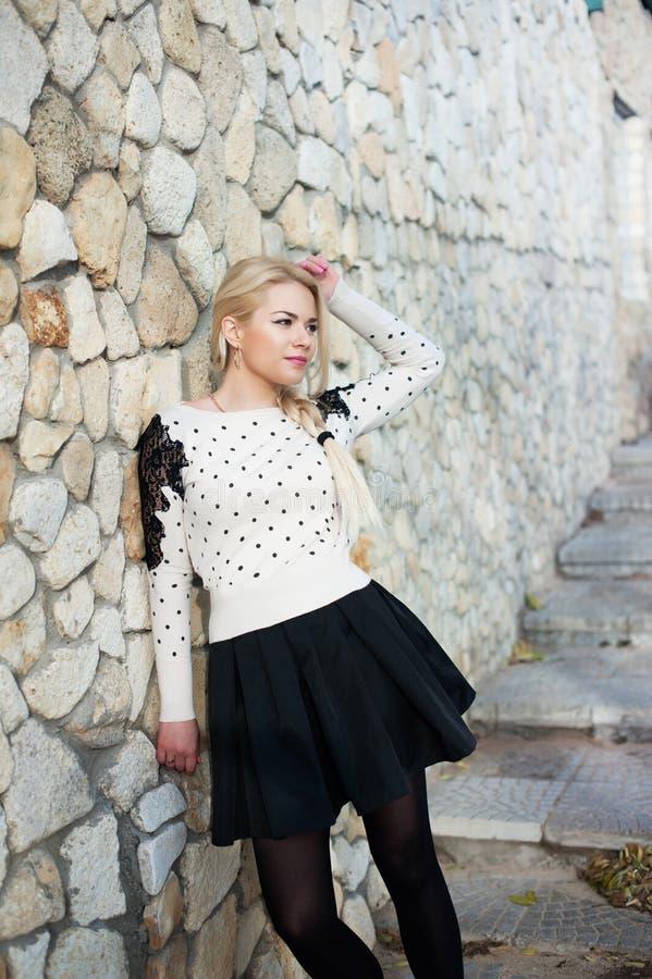 Jovem mulher bonita que vai perto da parede de pedra imagens de stock
