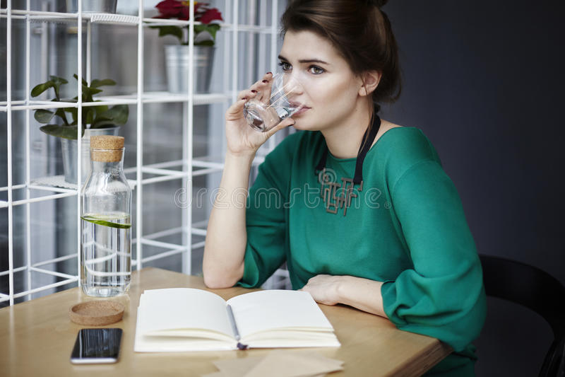 A jovem mulher bonita que veste a água pura bebendo verde no café, comendo o café da manhã, livro aberto espalhou na tabela foto de stock