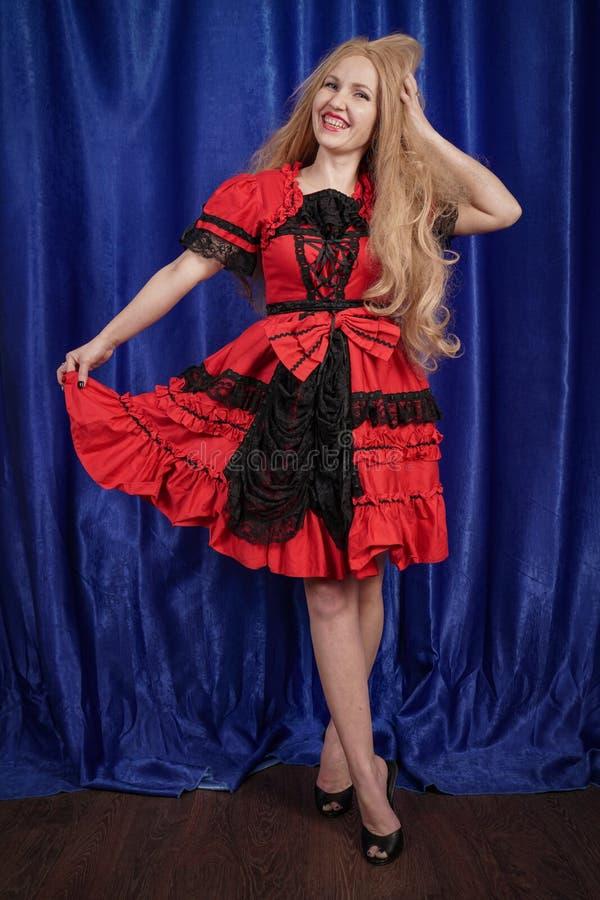 Jovem mulher bonita que veste o vestido vermelho do Dia das Bruxas do faitytale no fundo azul foto de stock