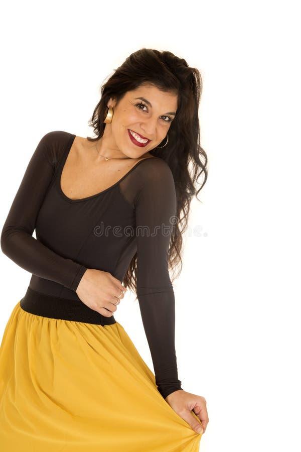 Jovem mulher bonita que veste uma parte superior preta e uma saia amarela fotografia de stock