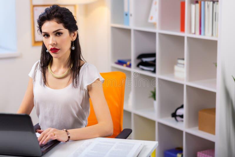 Jovem mulher bonita séria com os bordos vermelhos que sentam-se em seu escritório fotos de stock royalty free