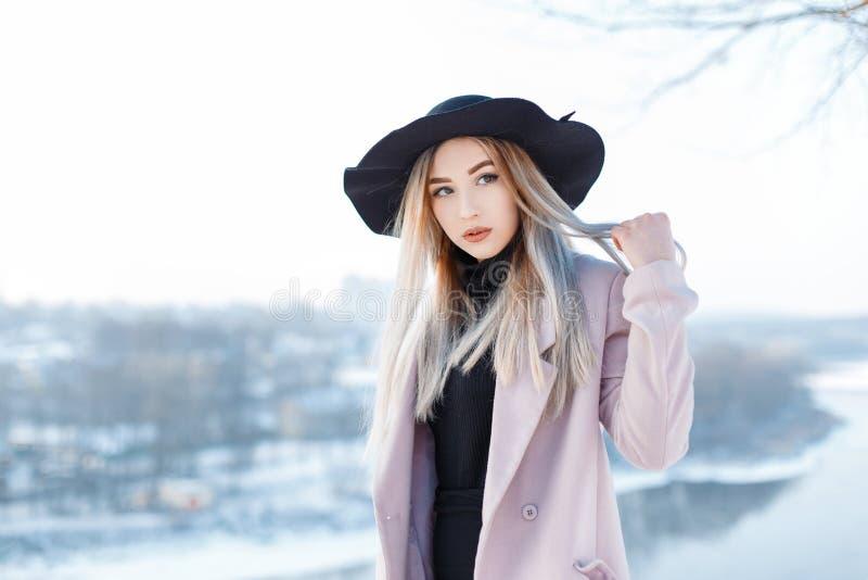 Jovem mulher bonita sensual com cabelo louro em um chapéu do vintage em um revestimento do rosa do inverno no estilo retro imagem de stock